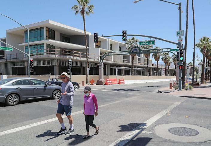 People walk around downtown Palm Springs with and without masks, May 24, 2021.