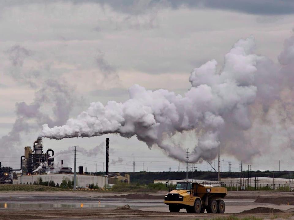 A dump truck works near the Syncrude oil sands extraction facility near Fort McMurray, Alta., in June 2014. A new survey in Saskatchewan found about 73 per cent of respondents agree the provincial government should take action to address climate change, but when asked how soon fossil fuels should be phased out, the most common answer was 'never.' (Jason Franson/The Canadian Press - image credit)