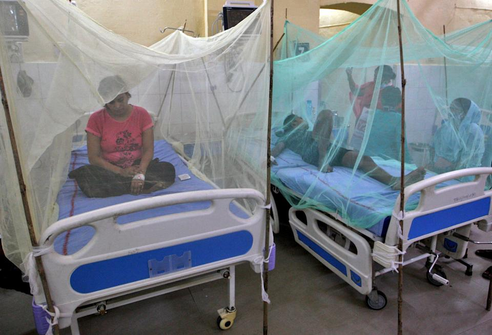 Dengue-infected patients sit under the mosquito nets after being hospitalised at Tej Bahadur Sapru Hospital in Prayagraj, in the northern state of Uttar Pradesh, India, September 13, 2021. REUTERS/Jitendra Prakash