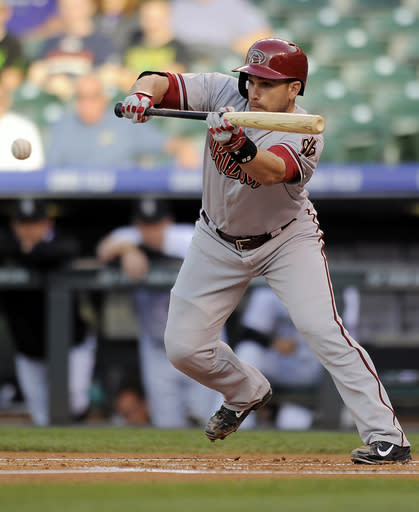 Arizona Diamondbacks Miguel Montero hits a bunt single in the first inning of a baseball game against the Colorado Rockies on Thursday, June 5, 2014, in Denver. (AP Photo/Chris Schneider)