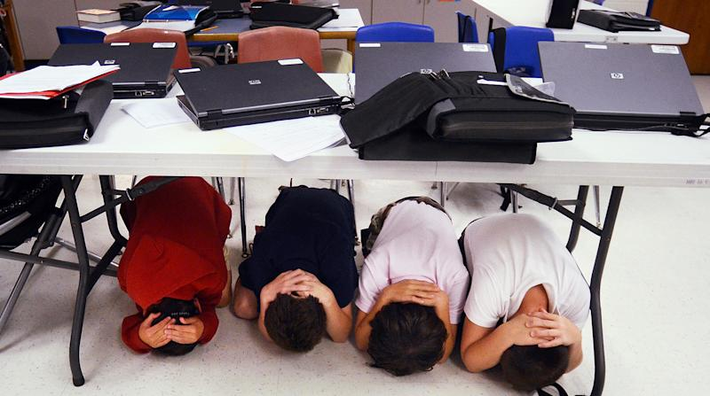"Fifth-graders take cover under a table during an earthquake drill at Hilton Head Island Elementary School on Thursday, Oct. 18, 2012. The drill was part of the 2012 Great Southeast ""ShakeOut,"" sponsored by the Federal Emergency Management Agency. (AP Photo/The Island Packet, Jay Karr)"