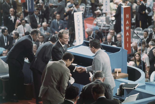 <p>The Rev. Billy Graham (center) is greeted on the podium of the 1968 Democratic National Convention in Chicago on Aug. 27, 1968. (Photo: AP) </p>