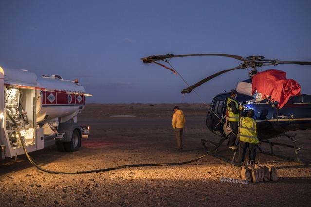 In this Sunday, Jan. 12, 2020 photo, APSCO employees fill a tank of a Dakar helicopter at the end of stage seven in Wadi Al Dawasir, Saudi Arabia. Formerly known as the Paris-Dakar Rally, the race was created by Thierry Sabine after he got lost in the Libyan desert in 1977. Until 2008, the rallies raced across Africa, but threats in Mauritania led organizers to cancel that year's event and move it to South America. It has now shifted to Saudi Arabia. The race started on Jan. 5 with 560 drivers and co-drivers, some on motorbikes, others in cars or in trucks. Only 41 are taking part in the Original category. (AP Photo/Bernat Armangue)
