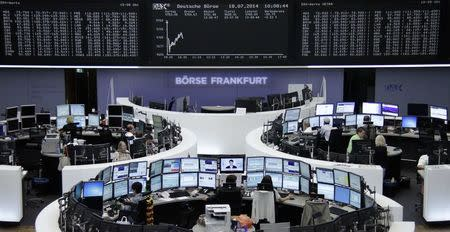 Traders are pictured at their desks in front of the DAX board at the Frankfurt stock exchange July 18, 2014. REUTERS/Remote/Stringer