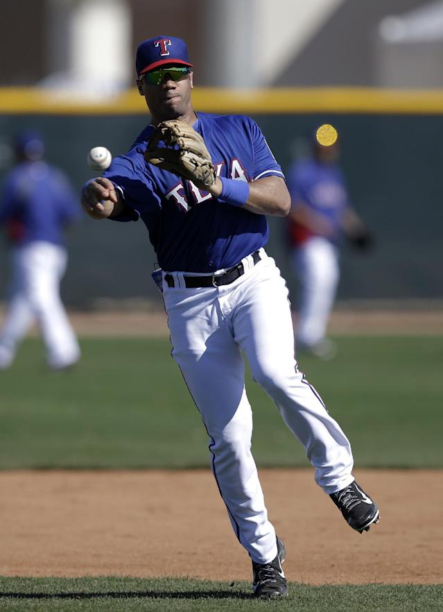 Seattle Seahawks quarterback Russell Wilson throws to first after fielding ground ball at second with the Texas Rangers during spring training baseball practice, Monday, March 3, 2014, in Surprise, Ariz. (AP Photo/Tony Gutierrez)