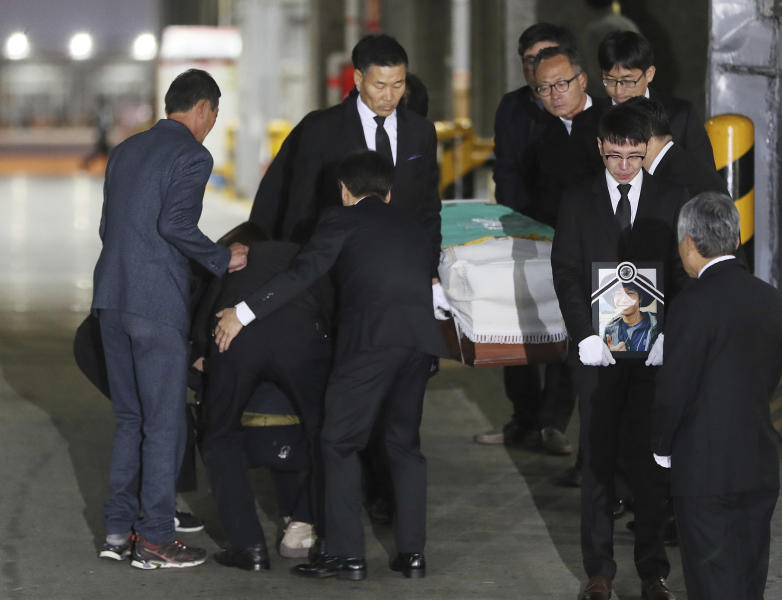 Family members of late mountain climber Lee Jae-hoon mourn as a casket carrying his body arrives at a cargo terminal at Incheon International Airport in Incheon, South Korea, Wednesday, Oct. 17, 2018. Relatives dressed in black funeral suits wept in grief on Wednesday as the bodies of five South Korean mountain climbers arrived home from Nepal where they had died in a storm last week. (Lee Ji-eun/Yonhap via AP)