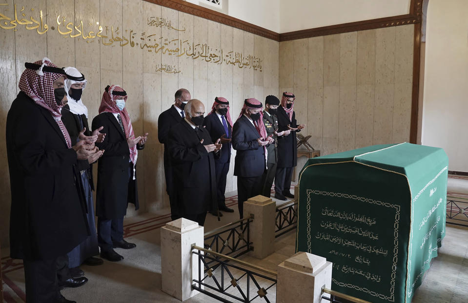 This photo from the Royal Court twitter account, shows Jordan's King Abdullah II, third right, Prince Hassan bin Talal, fifth right, Prince Hamzah bin Al Hussein, seventh right, and others pray during a visit to the tomb of the late King Abdullah I, in Amman Jordan, Sunday, April 11, 2021. King Abdullah II and his half brother Prince Hamzah have made their first joint public appearance since a palace feud last week. Members of the Jordanian royal family Sunday marked the centenary of the establishment of the Emirate of Transjordan, a British protectorate that preceded the kingdom. (Royal Court Twitter Account via AP)