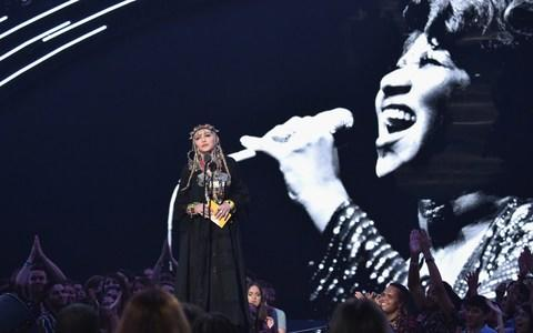 An enormous picture of Aretha Franklin is seen behind Madonna as she spoke of prostitution and crack-houses - Credit: John Shearer/Getty Images for MTV