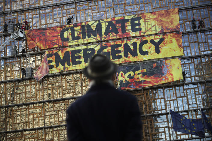 FILE - In this file photo dated Thursday, Dec. 12, 2019, a man looks up as police and fire personnel move in to remove climate activists and their banner, after they climbed the Europa building during a demonstration outside an EU summit meeting in Brussels. Massive challenges lay ahead for the European Union in 2020, as the impact of climate change seems likely to drive the bloc's thinking and policy initiatives over the coming years, starting Wednesday Jan. 1, 2020. (AP Photo/Francisco Seco, FILE)