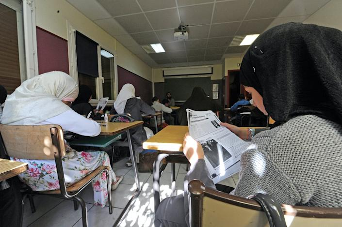 Pupils in headscarves sit at desks