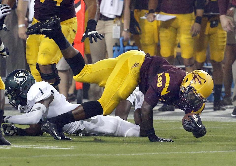 Sacramento State's Osagie Odiase (1) trips up Arizona State's Marion Grice, right, during the first half in an NCAA college football game on Thursday, Sept. 5, 2013, in Tempe, Ariz. (AP Photo/Ross D. Franklin)