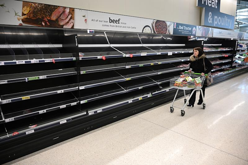A shopper walks past empty food shelves amidst the novel coronavirus COVID-19 pandemic, in Manchester, northern England on March 20, 2020. - The British prime minister urged people in his daily press conference on March 19 to be reasonable in their shopping as supermarkets emptied out of crucial items -- notably toilet roll -- across Britain. The government said it was temporarily relaxing elements of competition law to allow supermarkets to work together to maintain supplies. (Photo by Oli SCARFF / AFP) (Photo by OLI SCARFF/AFP via Getty Images)