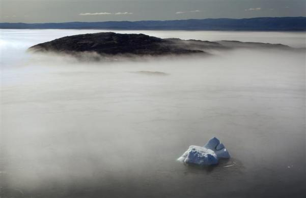 A large iceberg is seen on the edge of a morning fog over Frobisher Bay, Nunavut in the Canadian Arctic August 21, 2009.