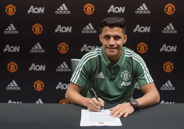 Alexis Sanchez poses while putting pen to paper as part of his Manchester United unveiling. (Getty)