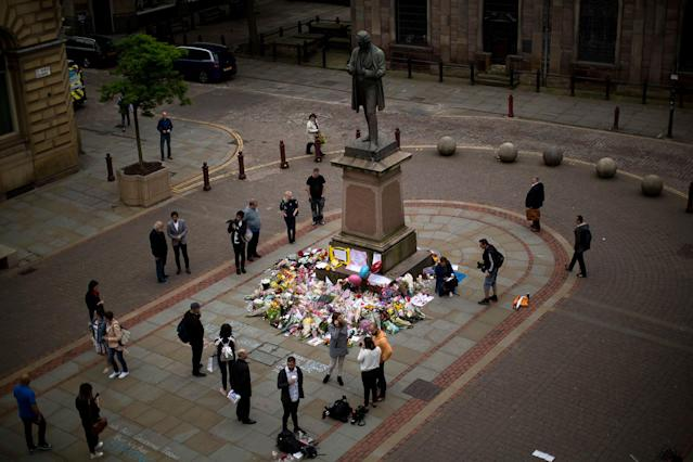 <p>People stand by flowers offered for the victims of a suicide attack at a concert by Ariana Grande that killed more than 20 people Monday night in central Manchester, Britain, Wednesday, May 24, 2017. (AP Photo/Emilio Morenatti) </p>