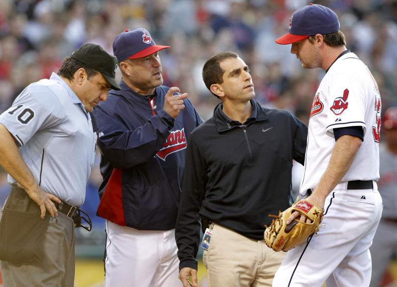 Cleveland Indians trainer Lonnie Soloff, second from right, talks with Indians starting pitcher Alex White, right, after White appeared to suffer a problem with his throwing hand against the Cincinnati Reds in the second inning of an interleague baseball game, Friday, May 20, 2011, in Cleveland.  At left are home plate umpire Phil Cuzzi and Cleveland Indians manager Manny Acta. (AP Photo/Amy Sancetta)