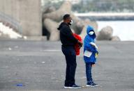 A migrant father and his son wait to be transferred by the police, in the port of Arguineguin