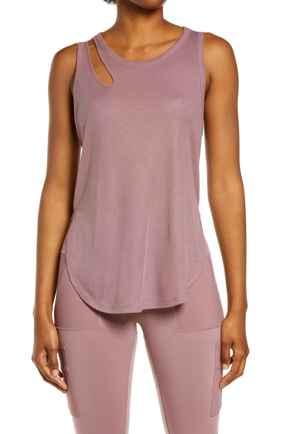 """<p><strong>Alo</strong></p><p>nordstrom.com</p><p><strong>$48.00</strong></p><p><a href=""""https://go.redirectingat.com?id=74968X1596630&url=https%3A%2F%2Fwww.nordstrom.com%2Fs%2Falo-peak-cutout-tank%2F5913181&sref=https%3A%2F%2Fwww.prevention.com%2Ffitness%2Fworkout-clothes-gear%2Fg37542513%2Fworkout-tops-for-women%2F"""" rel=""""nofollow noopener"""" target=""""_blank"""" data-ylk=""""slk:Shop Now"""" class=""""link rapid-noclick-resp"""">Shop Now</a></p><p>This sleeveless tank is <strong>made from a soft ribbed fabric that's lightweight and stretchy</strong>. The features include an asymmetrical cut out in the front and back, as well as a high-low hem with side slits. Pair it with your favorite <a href=""""https://www.prevention.com/fitness/workout-clothes-gear/g34943640/plus-size-workout-clothes/"""" rel=""""nofollow noopener"""" target=""""_blank"""" data-ylk=""""slk:sports bra"""" class=""""link rapid-noclick-resp"""">sports bra</a> and biker shorts for a complete look. </p>"""