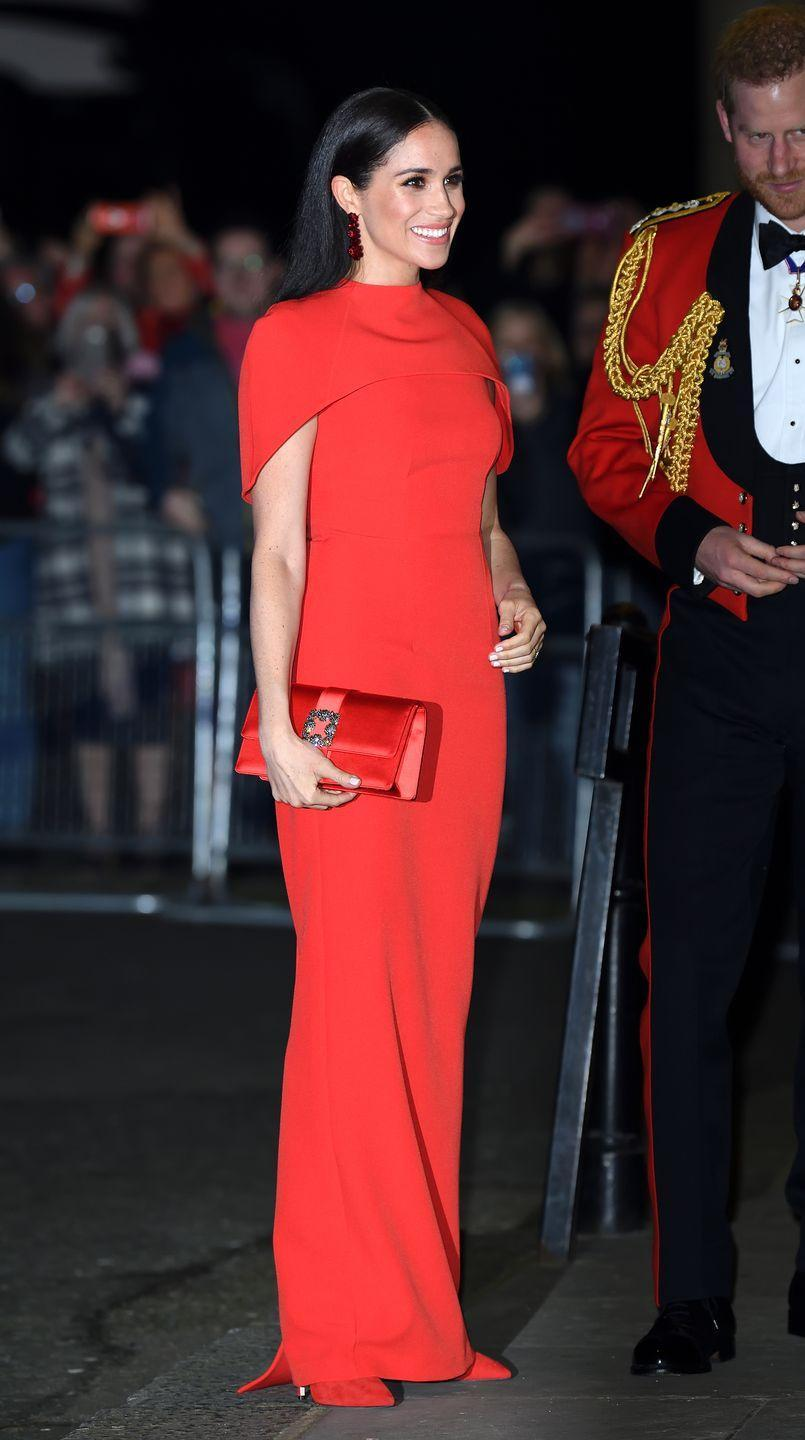 """<p>The royal wore a stunning full-length crepe, caped, red dress <a href=""""https://www.safiyaa.com/products/kalika-long-dress"""" rel=""""nofollow noopener"""" target=""""_blank"""" data-ylk=""""slk:by Safiyaa"""" class=""""link rapid-noclick-resp"""">by Safiyaa</a> for the <a href=""""https://www.elle.com/uk/life-and-culture/a31269596/meghan-markle-prince-harry-mountbatten-festival-music/"""" rel=""""nofollow noopener"""" target=""""_blank"""" data-ylk=""""slk:event"""" class=""""link rapid-noclick-resp"""">event</a> at London's Royal Albert Hall.</p><p>The former actress wore her hair down, straight, for the event and accessorised with a red clutch bag. </p>"""