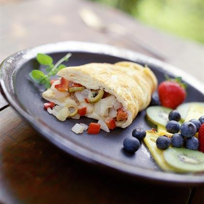 """<p>Stuff a traditional omelet with plenty of sliced <a href=""""https://www.myrecipes.com/t/vegetables/potatoes"""" rel=""""nofollow noopener"""" target=""""_blank"""" data-ylk=""""slk:potato,"""" class=""""link rapid-noclick-resp"""">potato,</a> onion, red bell pepper, olives, and mozzarella cheese for a Mediterranean twist on this classic brunch fare. Serve with fresh fruit. </p>"""