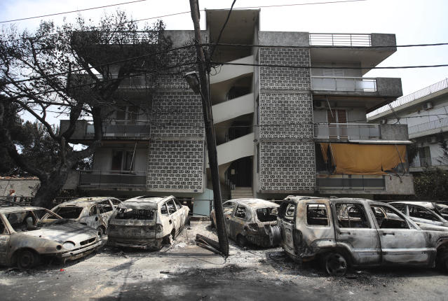 <p>Burned-out cars stand outside an apartment block in Mati east of Athens, Tuesday, July 24, 2018. (Photo: Thanassis Stavrakis/AP) </p>