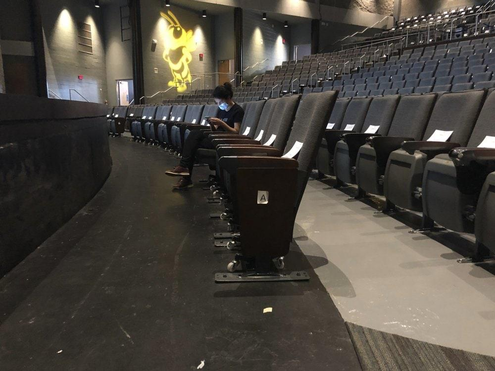 A graduate assistant sits in an empty auditorium during an online lecture on the first day of classes Monday, August 17, 2020, at Georgia Tech in Atlanta. (AP Photo/Jeff Amy)