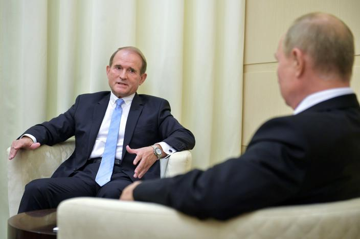 Ukrainian tycoon Viktor Medvedchuk, left, speaks to Russian President Vladimir Putin during a meeting at the Novo-Ogaryovo residence outside Moscow, Russia, Tuesday, Oct. 6, 2020. Medvedchuk, who heads the Opposition Platform for Life party and has close ties with Putin, was placed under house arrest on Thursday, May 13, 2021 by a Ukrainian court on treason charges that he denied. (Sputnik, Kremlin Pool Photo via AP)