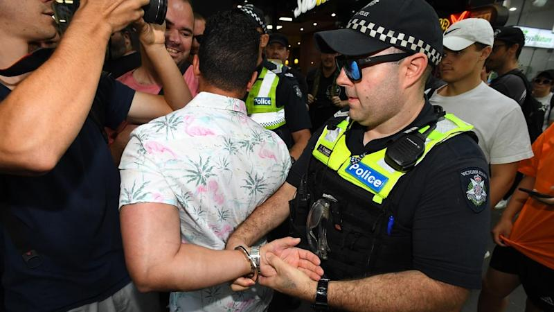 Far-right figure Avi Yemini was led away from Melbourne's Invasion Day marchers by police