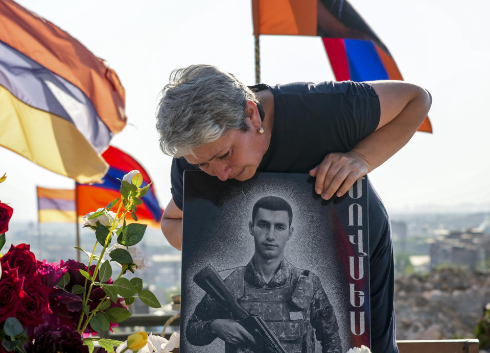Irina Harutyunyan, mother of Movses Harutyunyan, who was killed during the fighting over Nagorno-Karabakh in 2020 year, mourns at his gave at the military cemetery outside Yerevan, Armenia, Monday, June 14, 2021. Hostilities flared in late September 2020, and the Azerbaijani military pushed deep into Nagorno-Karabakh and nearby areas in six weeks of fighting involving heavy artillery and drones that killed more than 6,000 people. (AP Photo/Mstyslav Chernov)