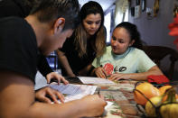 Claudia Bahena, 21, of Burlington, N.C., right, is helped to register to vote during a voter registration drive by community activists, in Burlington, N.C., Wednesday, March 11, 2020. At left is Lizet Miranda, who offered her home as a site for neighbors who are eligible to register. (AP Photo/Jacquelyn Martin)