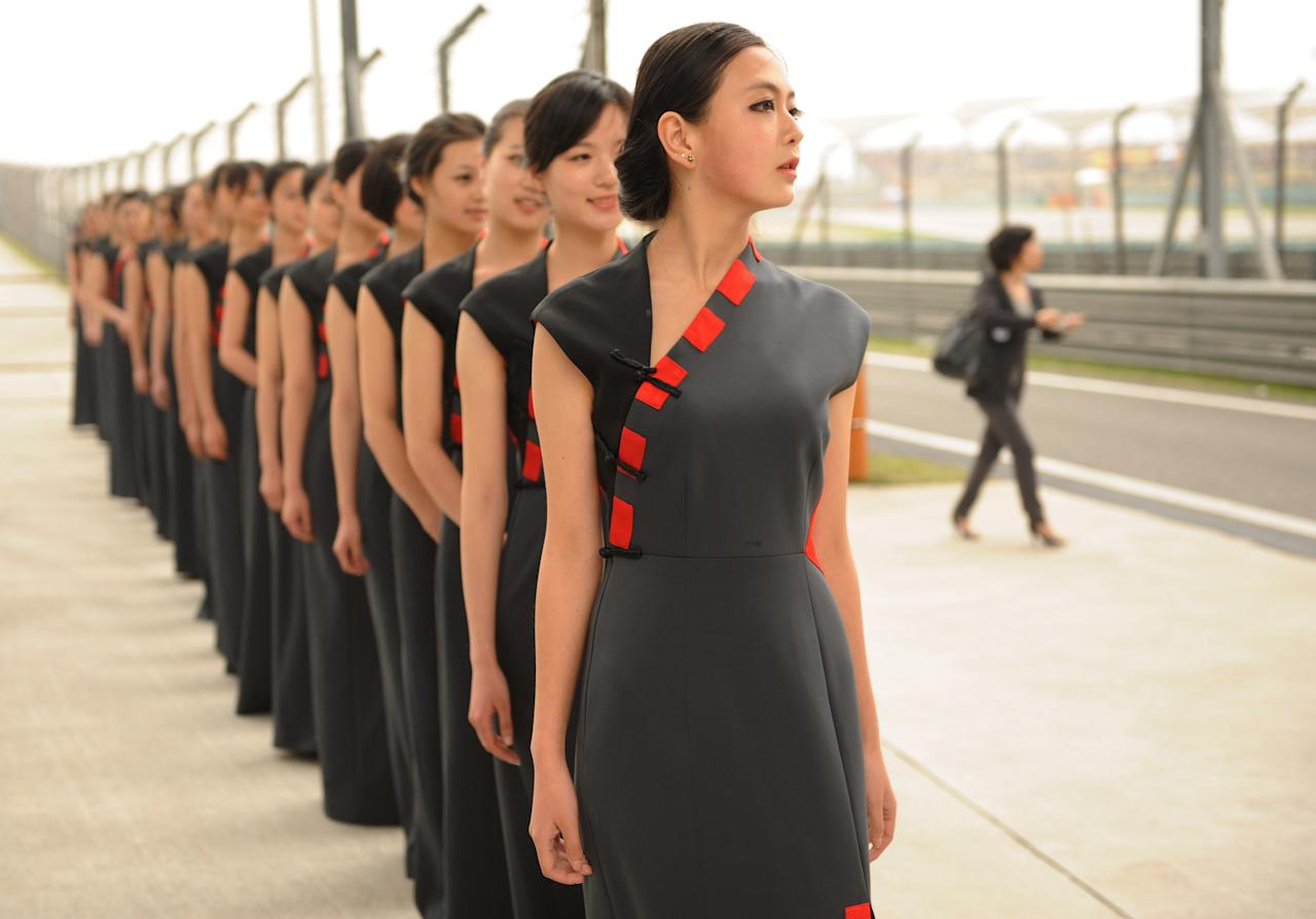 Chinese models parade through the pits after the third practice session for Formula One's Chinese Grand Prix at the Shanghai International Circuit on April 14, 2012. AFP PHOTO/Peter PARKS (Photo credit should read PETER PARKS/AFP/Getty Images)