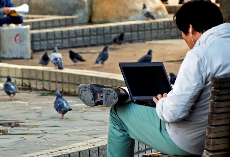 A man uses a laptop computer as pigeons are seen at a park in Tokyo, Japan. (Photo: REUTERS/Toru Hanai)