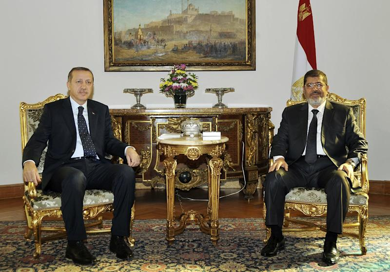 FILE -- In this Saturday, Nov. 17, 2012 file photo, released by the Egyptian Presidency, Turkish Prime Minister Recep Tayyip Erdogan, left, meets with Egyptian President Mohammed Morsi for the first time since the Egyptian Islamist leader was elected late June, in Cairo Egypt. Egypt downgraded diplomatic relations with Turkey and expelled its ambassador from Cairo, Saturday, Nov. 23, 2013, a sharp escalation in tensions between the two countries that mounted after a military coup ousted Morsi this summer. (AP Photo/Egyptian Presidency, File)