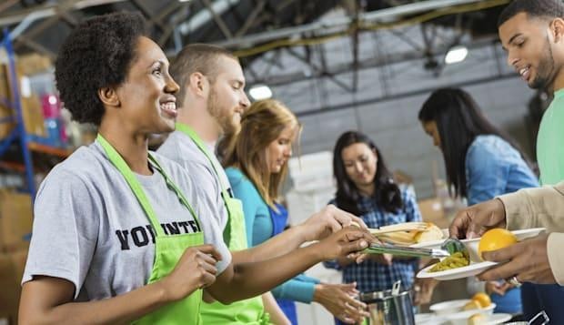 Volunteers serving healthy hot meal at soup kitchen