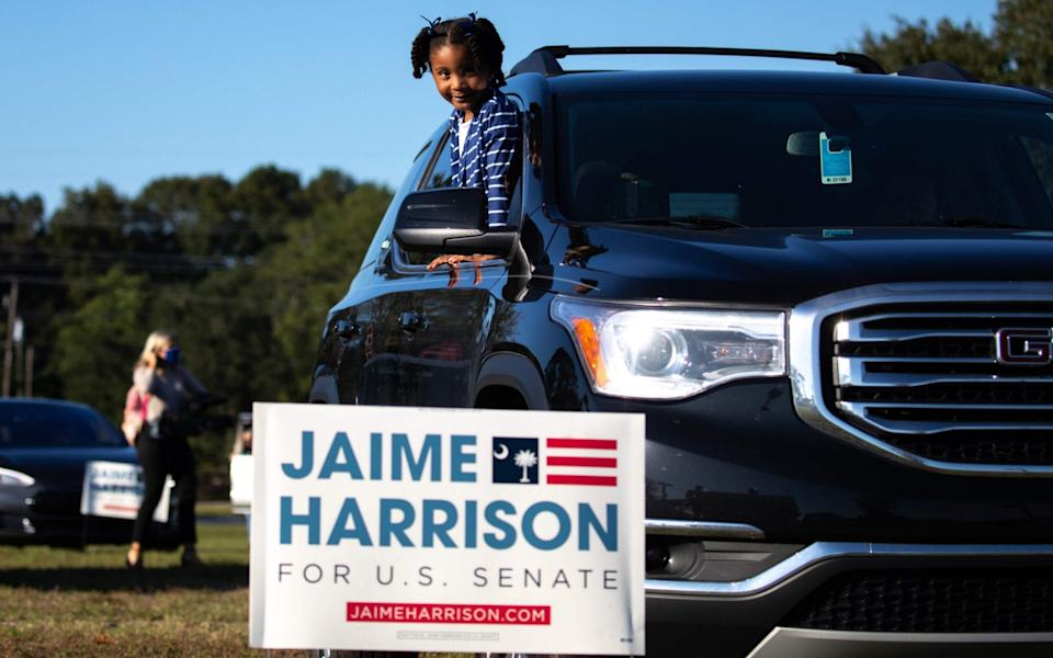 A young supporter of Democratic candidate for Senate Jaime Harrison looks on from her vehicle as he speaks during a socially distanced drive-in rally - AFP