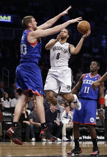 Brooklyn Nets guard Deron Williams (8) looks to pass over the defense of Philadelphia 76ers center Spencer Hawes (00) in the first half of an NBA basketball game, Tuesday, April 9, 2013, in New York. 76ers guard Jrue Holiday (11) watches the play. (AP Photo/Kathy Willens)