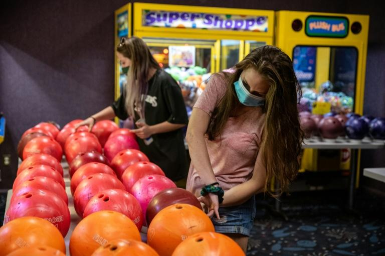 Texas was quick to begin reopening its economy -- bowlers pick up clean balls at Westgate Lanes in Austin, Texas in May 2020 -- but the state has now halted steps to reopen its economy after a sharp rise in coronavirus cases (AFP Photo/Sergio Flores)