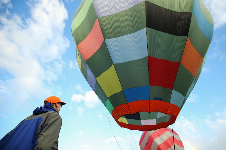 WELLINGTON, NEW ZEALAND - APRIL 15:  A spectator looks on as balloons inflate after poor weather kept pilots grounded during the Park to Paddock Challenge at the Wairarapa Balloon Festival on April 15, 2017 in Greytown, New Zealand. The Wairarapa Balloon Festival is an annual event and this year features two special international balloons - High Kitty from the United States, and Alien Rocket from Canada. The festival runs from 13 - 17 April, 2017.  (Photo by Hagen Hopkins/Getty Images)