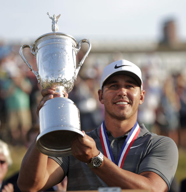 Brooks Koepka holds up the Golf Champion Trophy after winning the U.S. Open Golf Championship, Sunday, June 17, 2018, in Southampton, N.Y. (AP Photo/Julio Cortez)