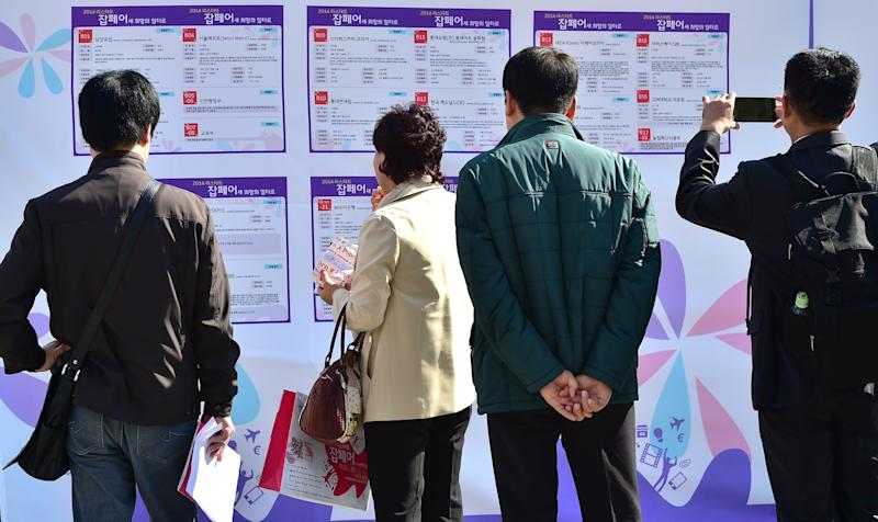 South Korean job seekers look at employment-offering notices, at a job fair in Seoul, on October 22, 2014 (AFP Photo/Jung Yeon-Je)