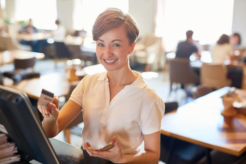 A restaurant owner processes a credit card payment for a meal.