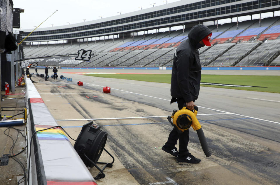 A crew member for Kyle Bush's team uses a blower to dry out the pit area before a NASCAR Cup Series auto race after morning rain prevented the 9 a.m. rescheduled start at Texas Motor Speedway in Fort Worth, Texas, Monday, Oct. 26, 2020. (AP Photo/Richard W. Rodriguez)