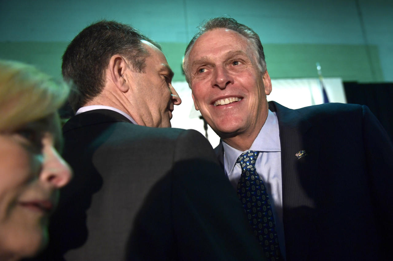 Virginia Gov. Ralph Northam, center, talks with former Virginia Gov. Terry McAuliffe, right, before the start of a news conference in the Crystal City neighborhood in Arlington, Va., Tuesday, Nov. 13, 2018. Amazon, which has grown too big for its Seattle hometown, said it will split its much-anticipated second headquarters between New York and northern Virginia. (AP Photo/Susan Walsh)