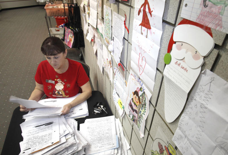 U. S. Postal Service employee Rita Rose  looks a some of thousands of Dear Santa letters that her office handles in Sacramento, Calif., Wednesday, Dec. 15, 2010.  The letters are on display so the public can read them and donate gifts that the post office will deliver to the families. (AP Photo)