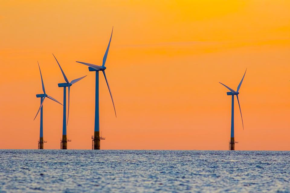 Offshore wind farm energy turbines at dawn. Surreal but natural sunrise at sea. Modernistic image. The future of clean energy production.