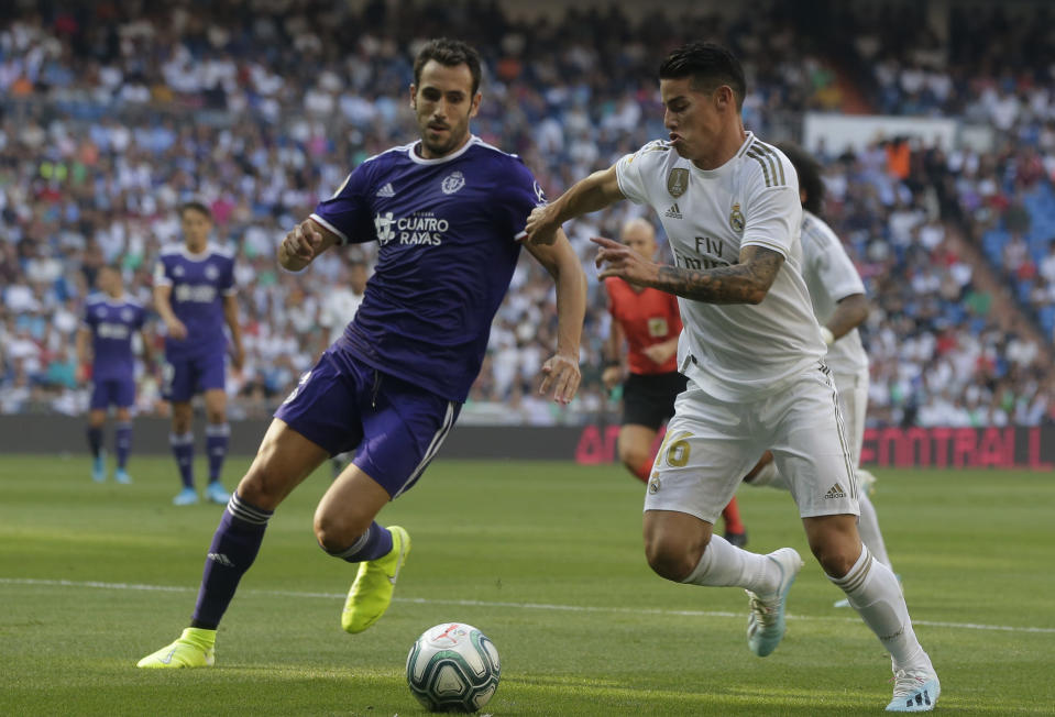 Real Madrid's James Rodriguez, right, vies for the ball with Valladolid's Kiko Olivas during the Spanish La Liga soccer match between Real Madrid and Valladolid at the Santiago Bernabeu stadium in Madrid, Spain, Saturday, Aug. 24, 2019. (AP Photo/Paul White)