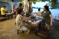 """Customers of the riverside Chaopraya Antique Café enjoy themselves despite the extraordinary high water levels in the Chao Phraya River in Nonthaburi, near Bangkok, Thailand, Thursday, Oct. 7, 2021. The flood-hit restaurant has become an unlikely dining hotspot after fun-loving foodies began flocking to its water-logged deck to eat amid the lapping tide. Now, instead of empty chairs and vacant tables the """"Chaopraya Antique Café"""" is as full as ever, offering an experience the canny owner has re-branded as """"hot-pot surfing."""" (AP Photo/Sakchai Lalit)"""