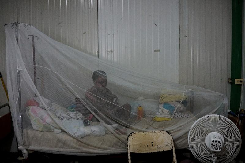 A patient sits on her bed protected by a net at a preoperative ward during the doctors' strike (AFP Photo/CHANDAN KHANNA)