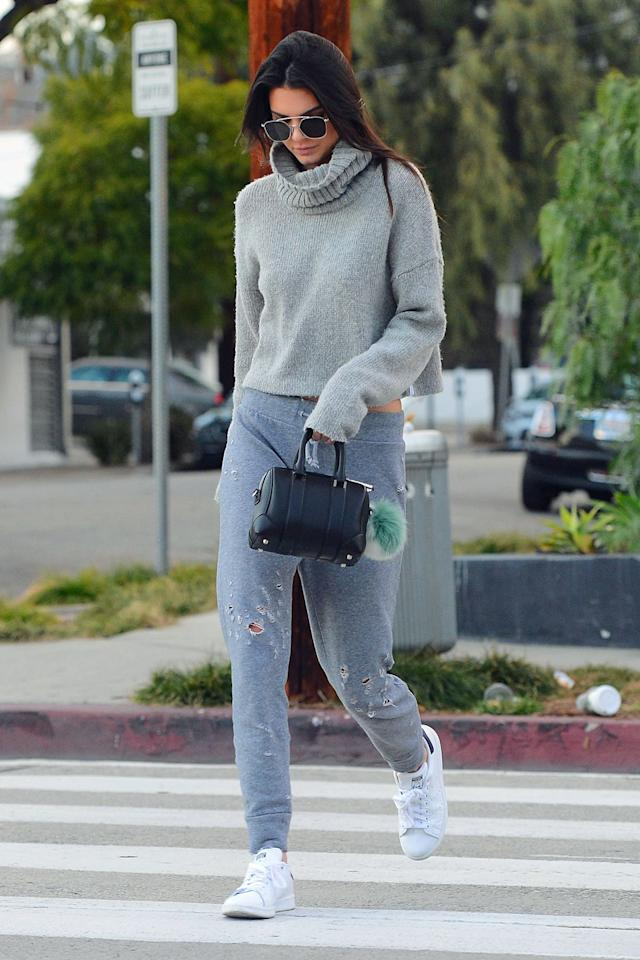 <p>Jenner made a coffee run wearing a slouchy gray turtleneck and distressed sweatpants paired with Stan Smith sneakers and a pompom-adorned mini bag. </p>