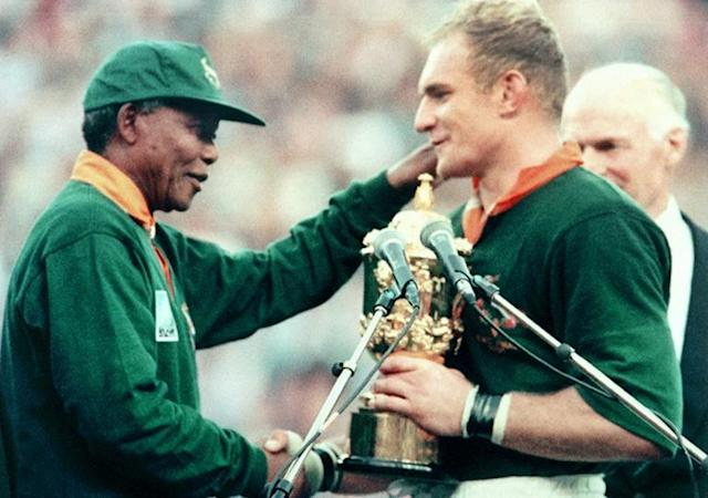 President Nelson Mandela (L) presents the Rugby World Cup trophy to captain Francois Pienaar after South Africa defeated New Zealand in the final in Johannesburg (AFP Photo/Jean-Pierre MULLER)